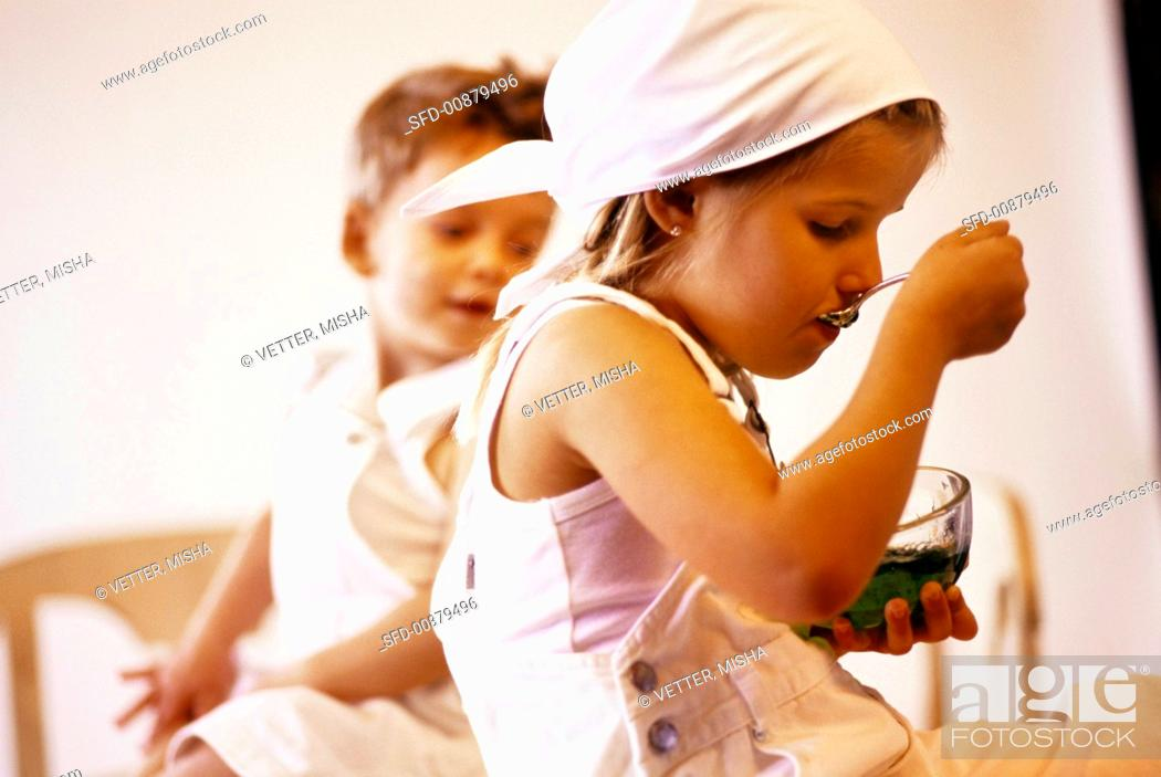 Stock Photo: Little girl eating jelly, little boy watching.