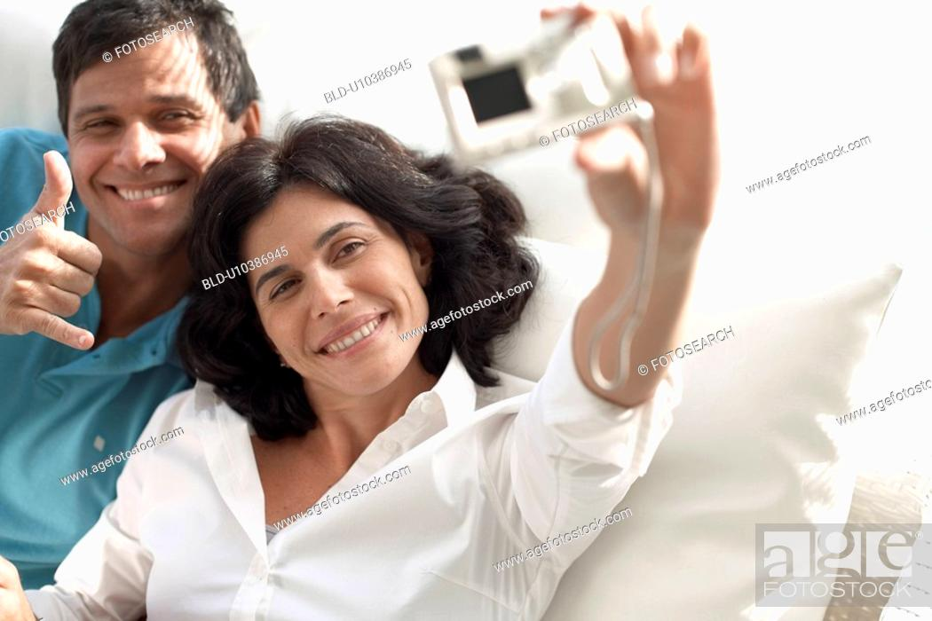 Stock Photo: Mid adult couple photographing themselves.