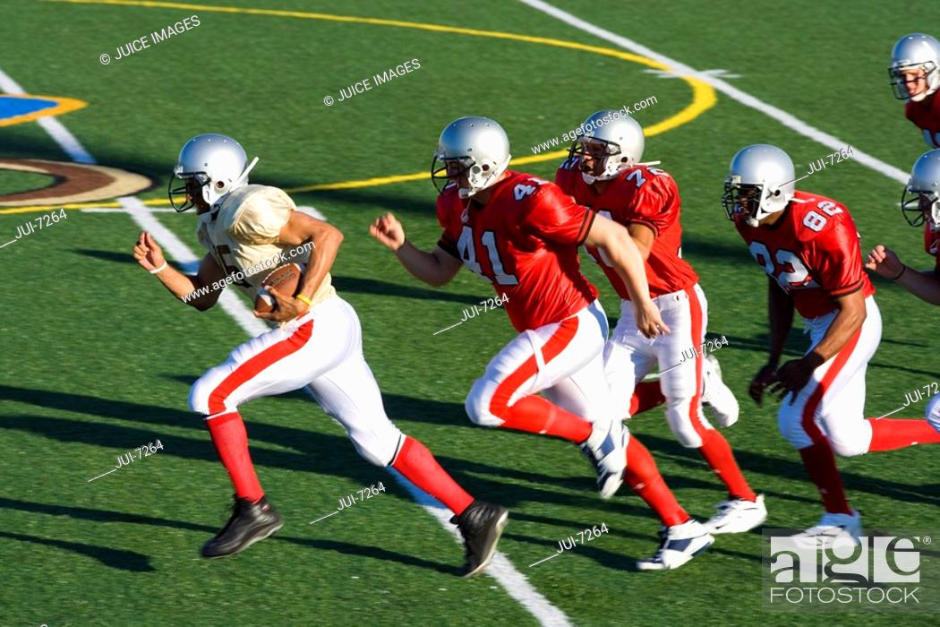 Stock Photo: American football players chasing opposing player running with ball at speed during competitive game, side view.