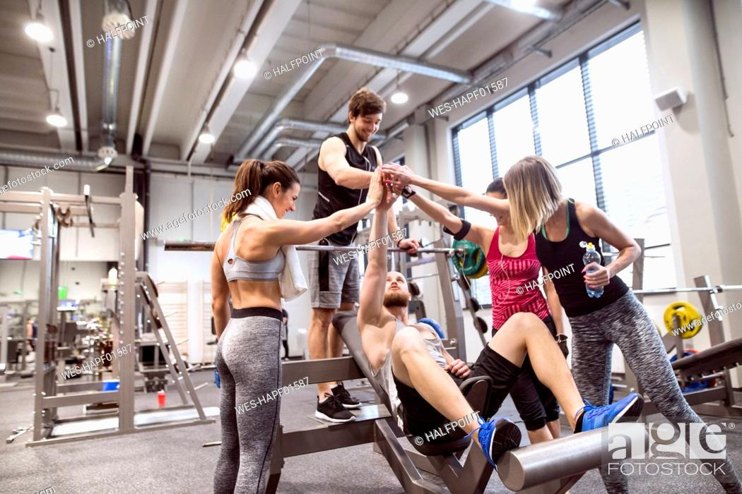 Stock Photo: Group of people in gym training weight lifting.