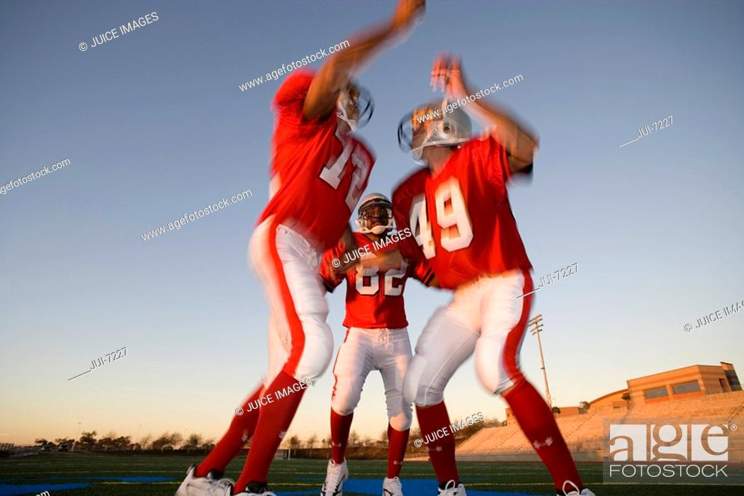 Stock Photo: Two American football players, in red football strips, celebrating touchdown on pitch at sunset, jumping chest to chest, teammate looking on, low angle view.