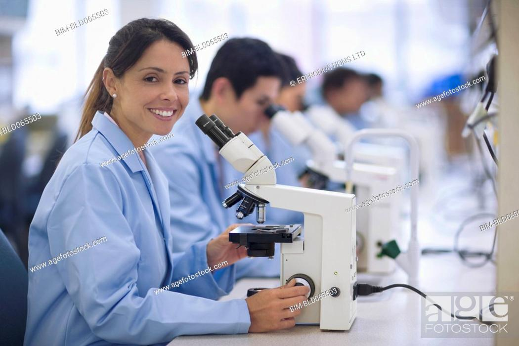 Stock Photo: Scientists working in laboratory with microscopes.