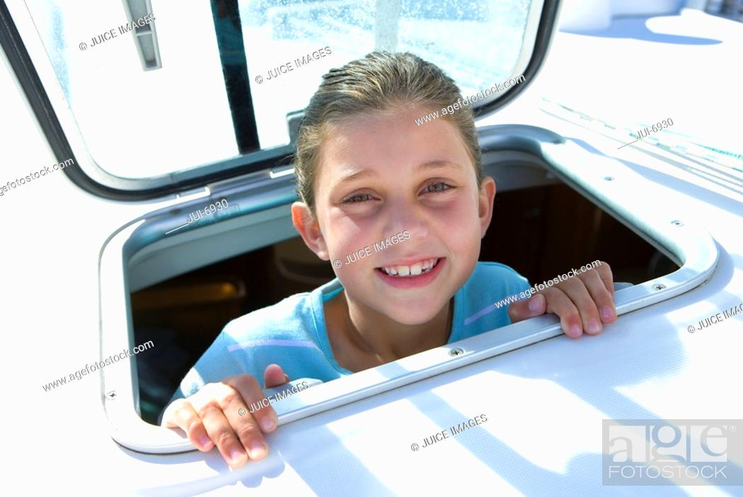 Stock Photo: Girl 8-10 sticking head through open sailing boat cabin window, smiling, close-up, portrait.