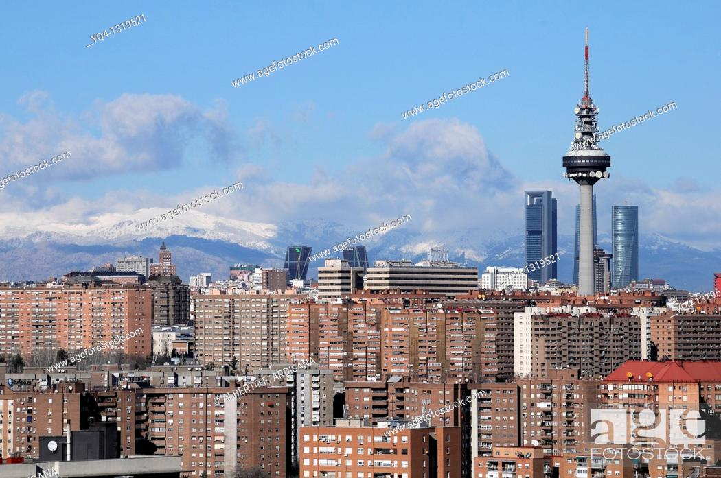 Stock Photo: Views from Madrid, with the Four Towers, telecoms tower 'Piruli', Kio Towers in the background and the Sierra of Madrid snowed.