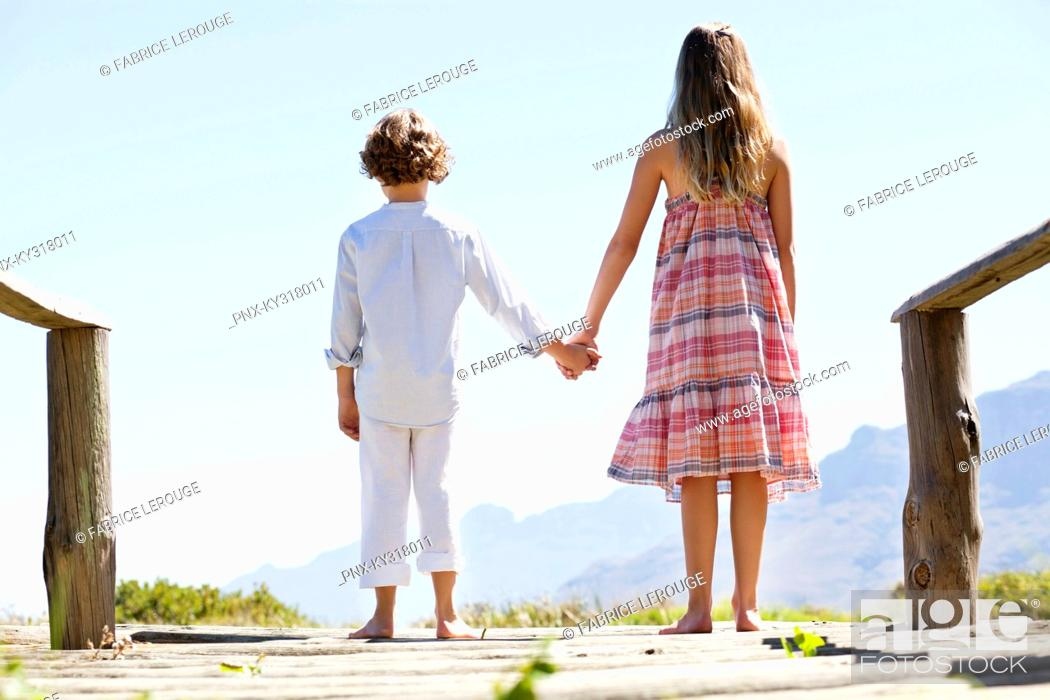 Stock Photo: Rear view of siblings standing together at a pier.