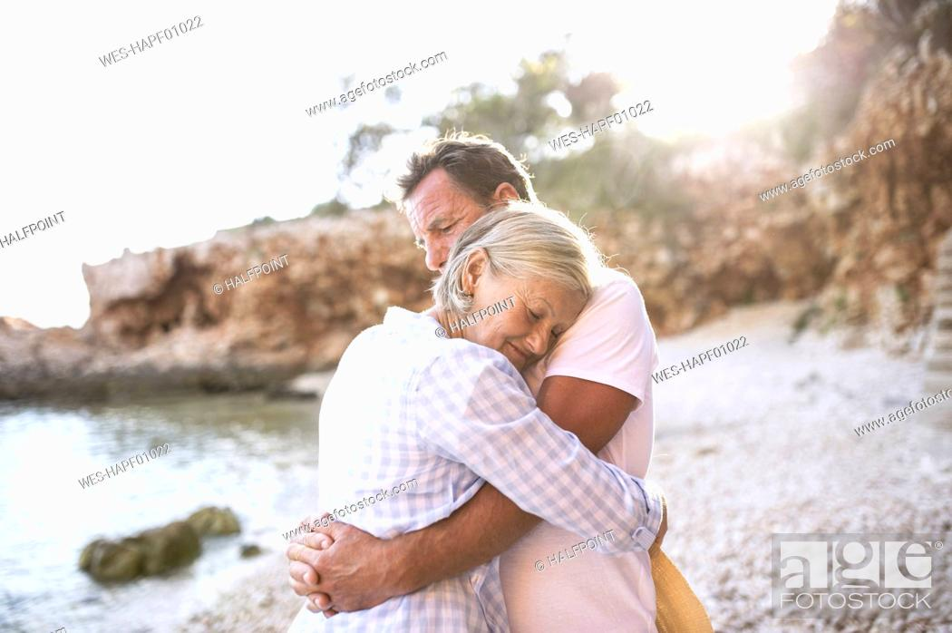 Photo de stock: Happy senior couple hugging on the beach.