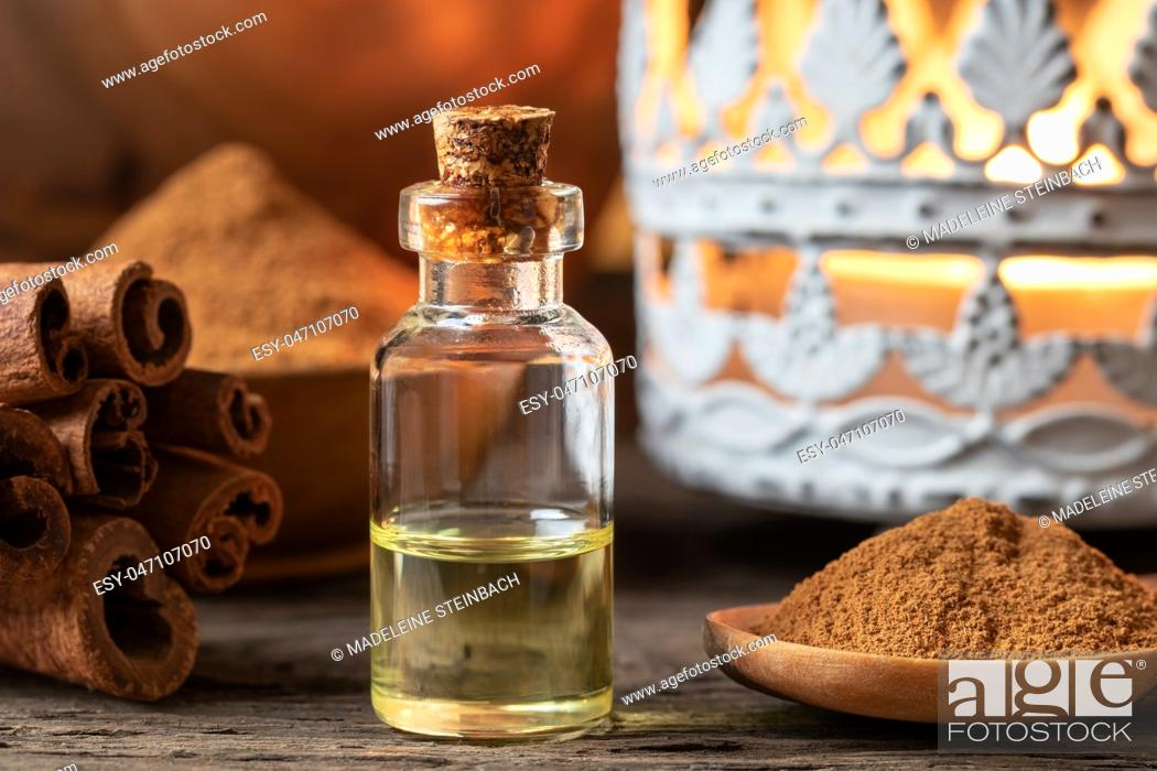 Stock Photo: A bottle of essential oil with cinnamon sticks and powder.