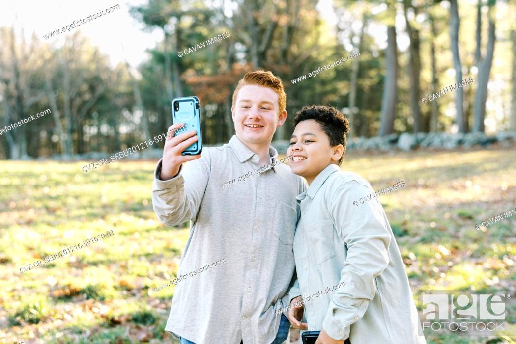 Stock Photo: Two tween mixed race brothers taking selfie together with smart phone.