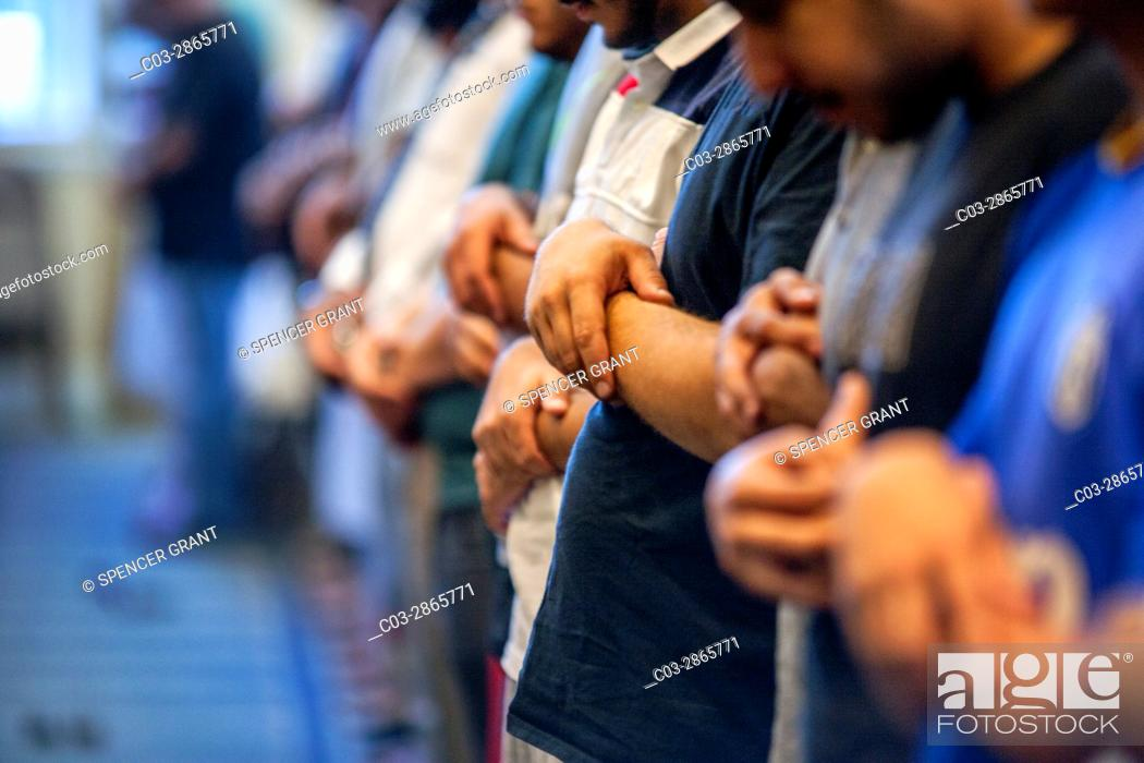 Stock Photo: Muslim men of many ages gather for Friday afternoon prayers during religious services at an Anaheim, CA, mosque. Clasped hand position indicates Sunni Muslim.
