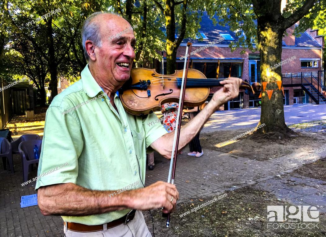 Stock Photo: Tilburg, Netherlands. Senior violin player performing his music during a neighborhood summer party.
