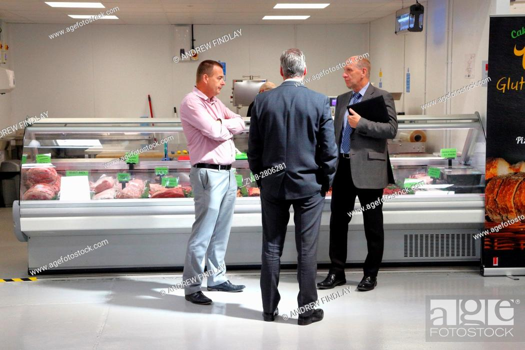 Stock Photo: Three men chatting in front of Butchery section of a food wholesaler.