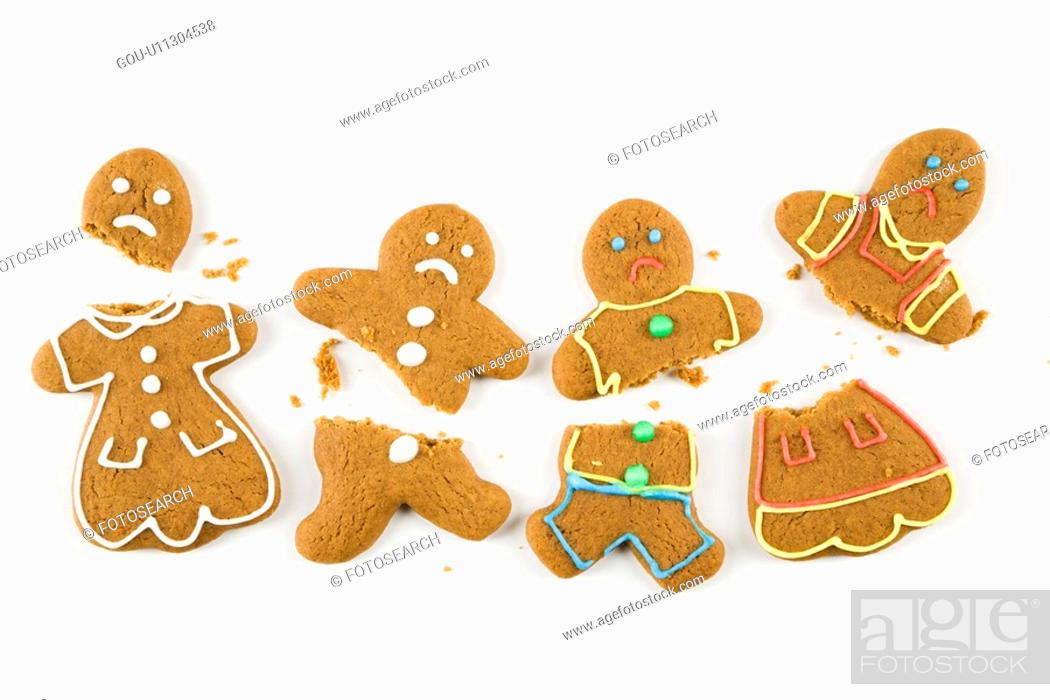 Stock Photo: Four frowning male and female gingerbread cookies broken into pieces.