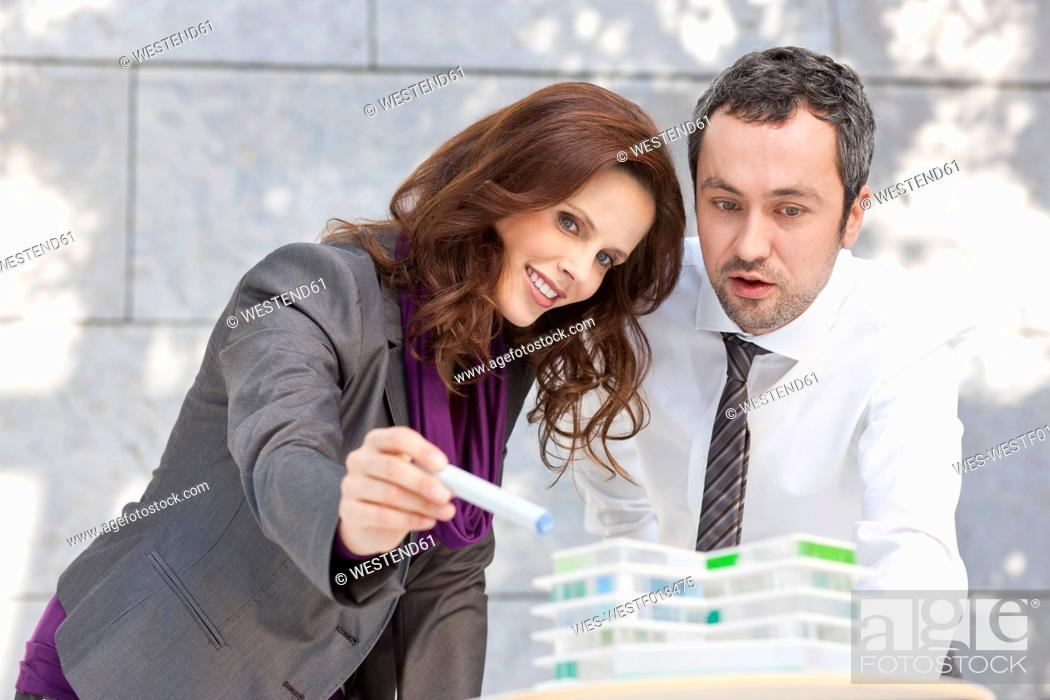 Stock Photo: Germany, Leipzig, Business people discussing about architectural model.