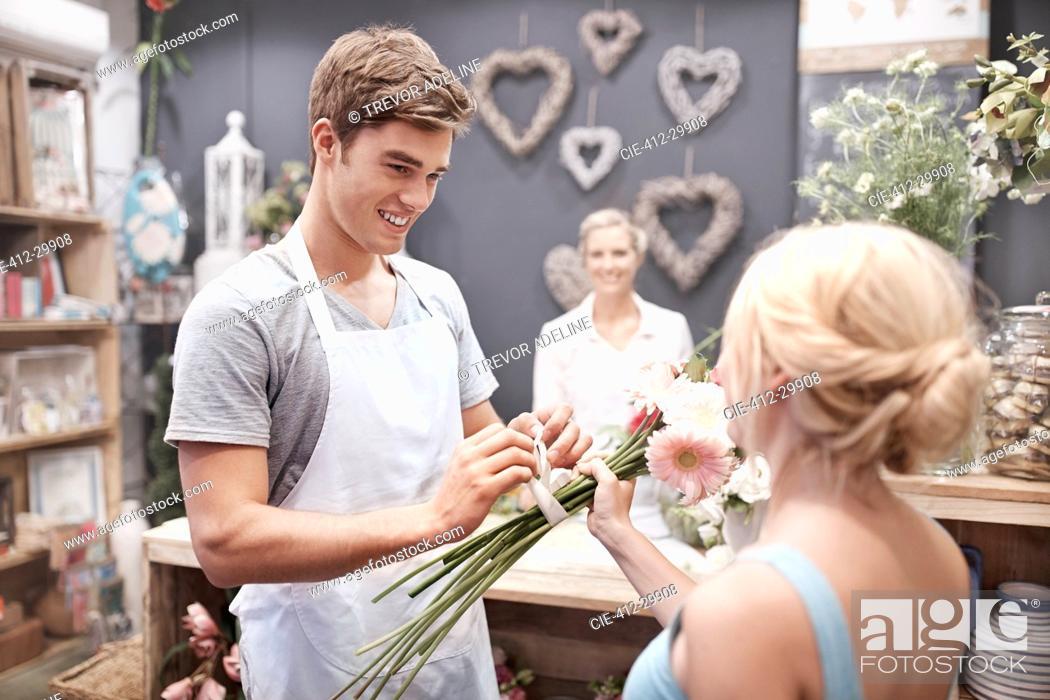 Stock Photo: Florist tying flowers for woman in flower shop.
