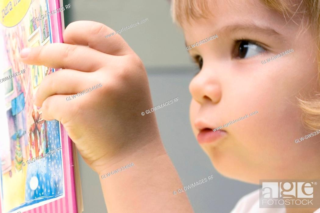 Stock Photo: Close-up of a boy reading a book.