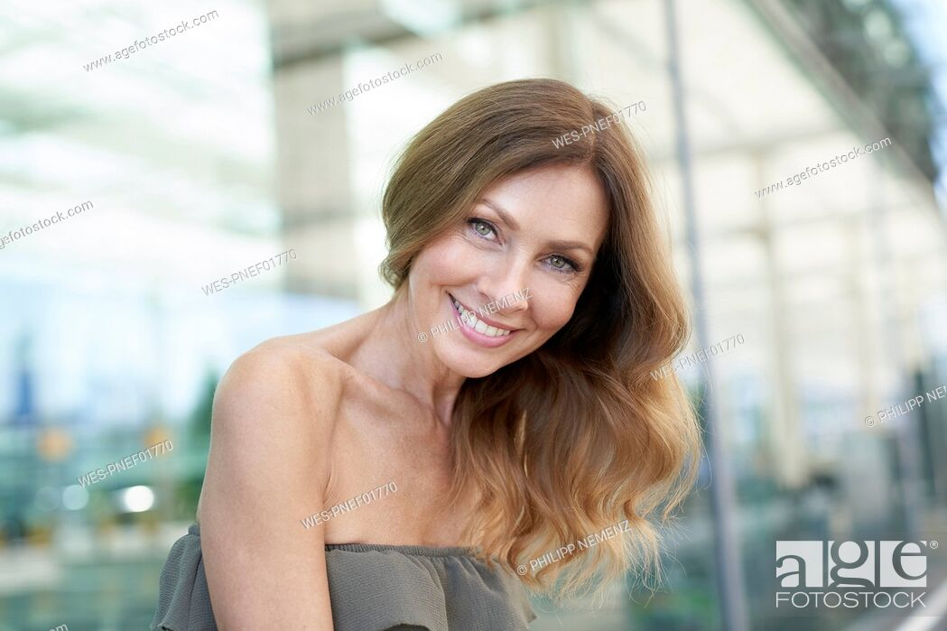 Stock Photo: Portrait of mature woman, glass facade in the background.