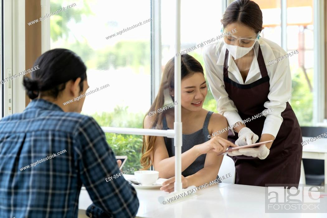 Stock Photo: Asian waitress wear facemask and face shield using tablet tp show restaurant electronic menu and recommend to customer. New normal technology and lifestyle food.