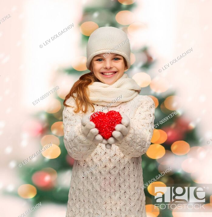 Stock Photo: seasonal, people, happiness , health, charity, love concept - smiling teenage girl in winter clothes with small red heart.