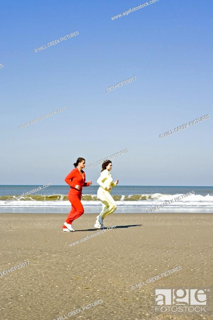 Stock Photo: Women jogging on beach.