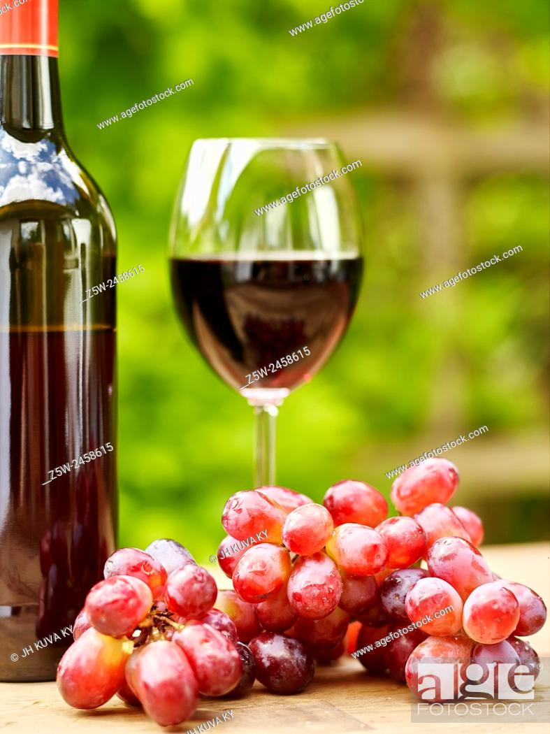 Stock Photo: Red Wine, Glass and Grapes on the table - focus on grapes, vertical format.