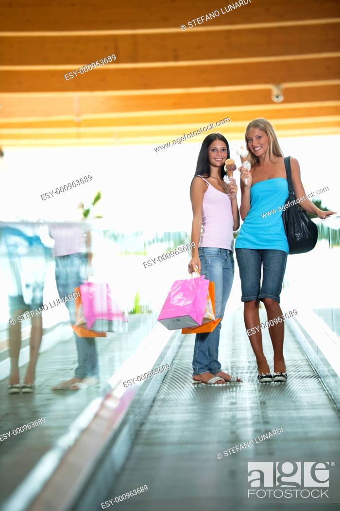 Stock Photo: Beautiful teenage girls on escalator at shopping center, eating ice-cream.