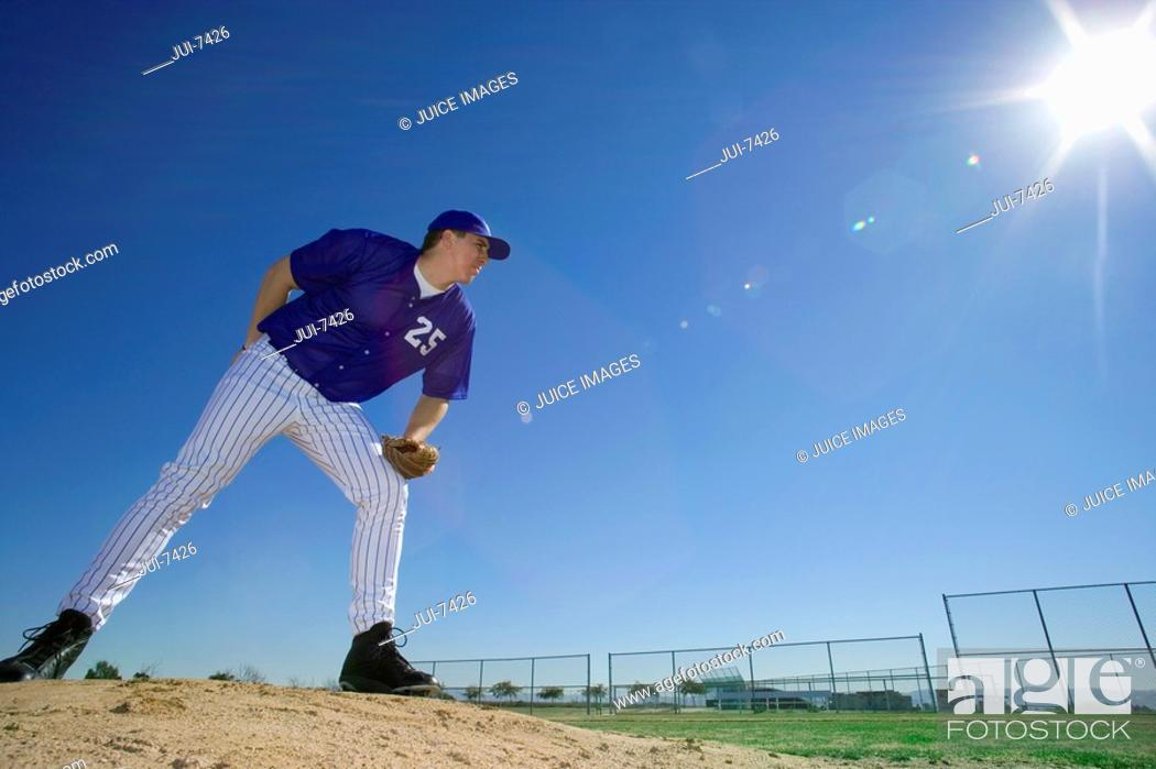 Stock Photo: Baseball pitcher, in blue uniform, preparing to throw ball during competitive game, holding ball behind back, side view lens flare, surface level.