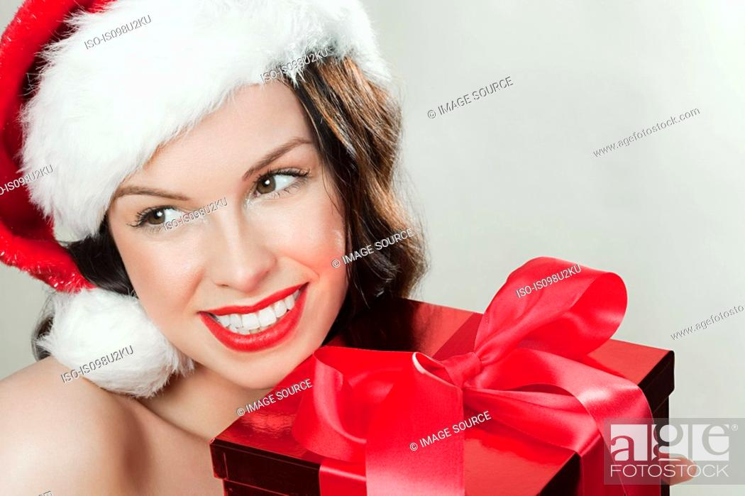Stock Photo: Young brunette woman wearing Santa hat with Christmas present.