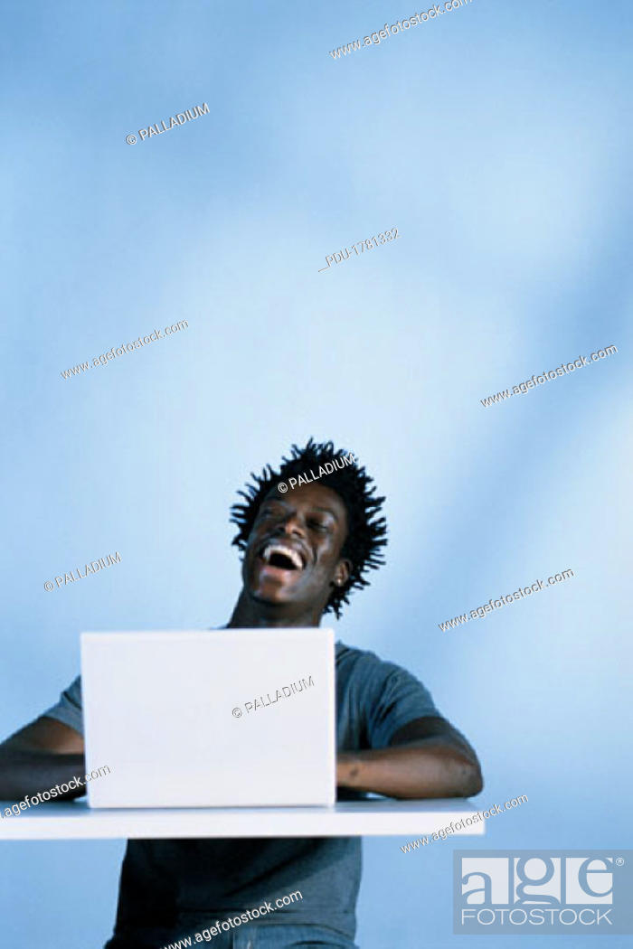 Stock Photo: Man with laptop computer, laughing.