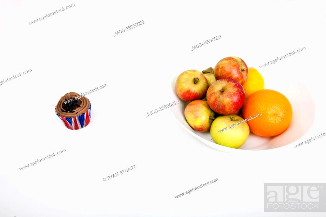 Stock Photo: Fresh fruits in plate with cupcake against white background.