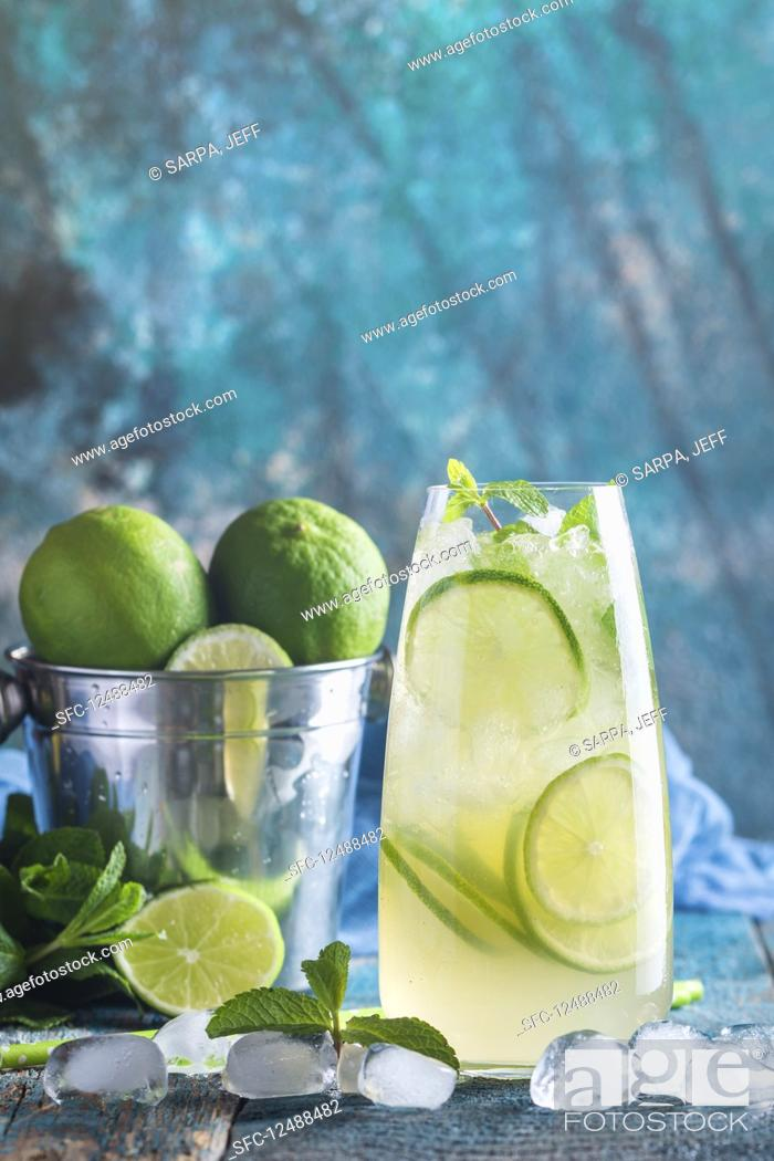 Imagen: Mojito cocktail with lime and mint in highball glass on blue background.