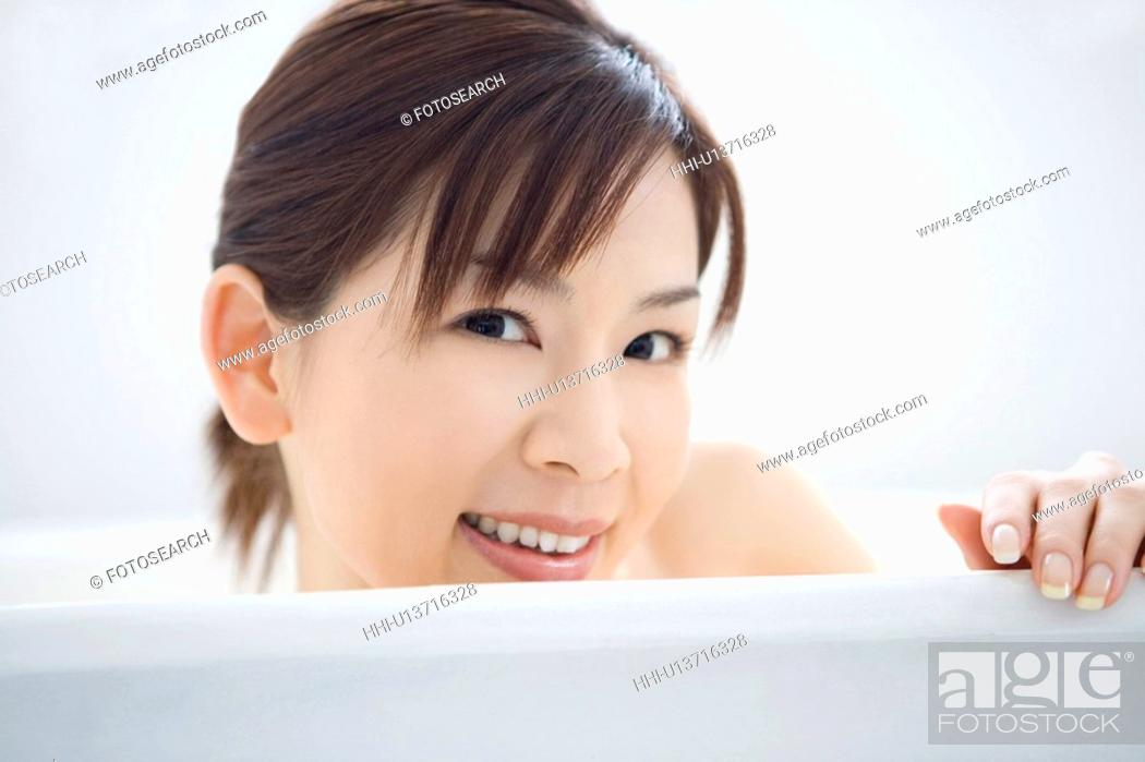 Stock Photo: Young woman in a bathtub, smiling, close up, front view.