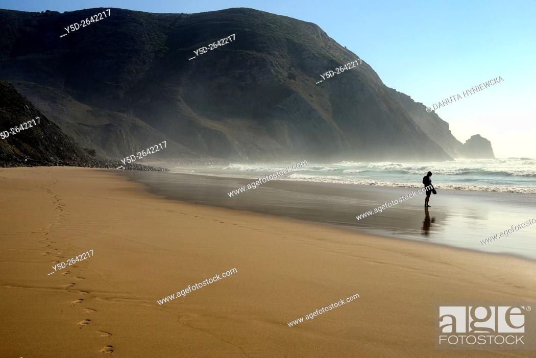 7c2f9a6ae Stock Photo - single man barefoot with shoes in hand on empty beach