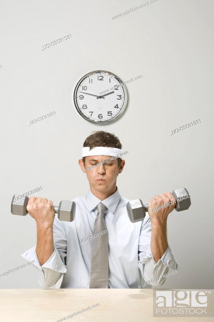 Stock Photo: Businessman lifting weights.
