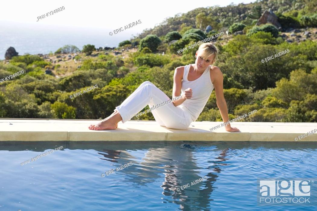 Stock Photo: Woman sitting at the poolside.