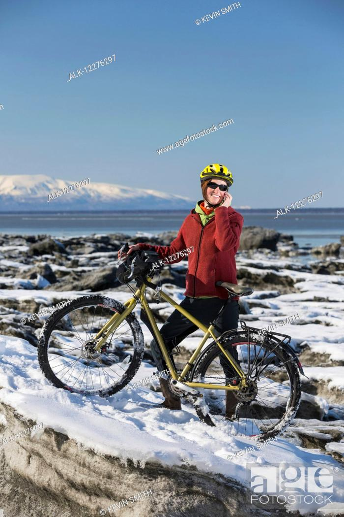 Imagen: A young woman stands with her bicycle on ice while talking on a cell phone next to the Tony Knowles Coastal Trail, Anchorage, Southcentral Alaska, USA.