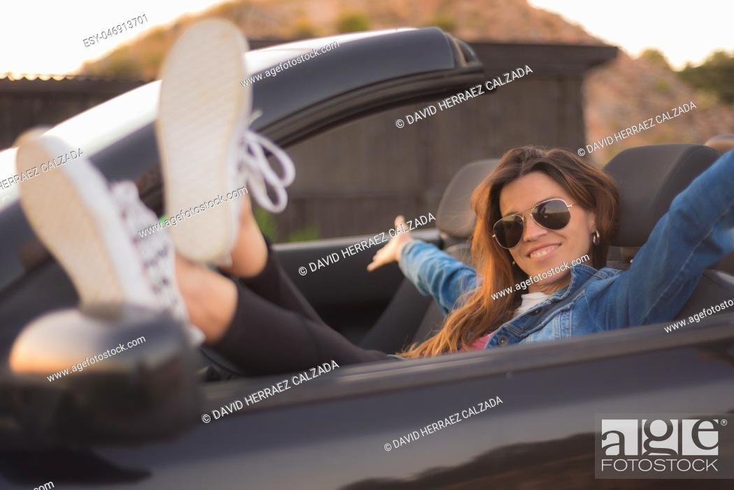 Stock Photo: Happy young woman enjoying her convertible car.