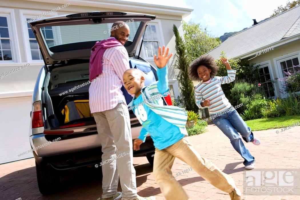 Stock Photo: Man loading back of car by daughter 8-10 chasing son 6-8, tilt.