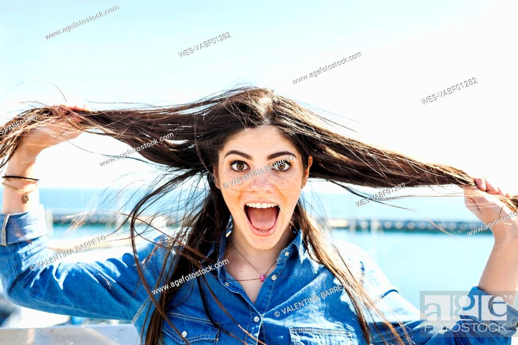 Stock Photo: Portrait of screaming young woman pulling her hair.
