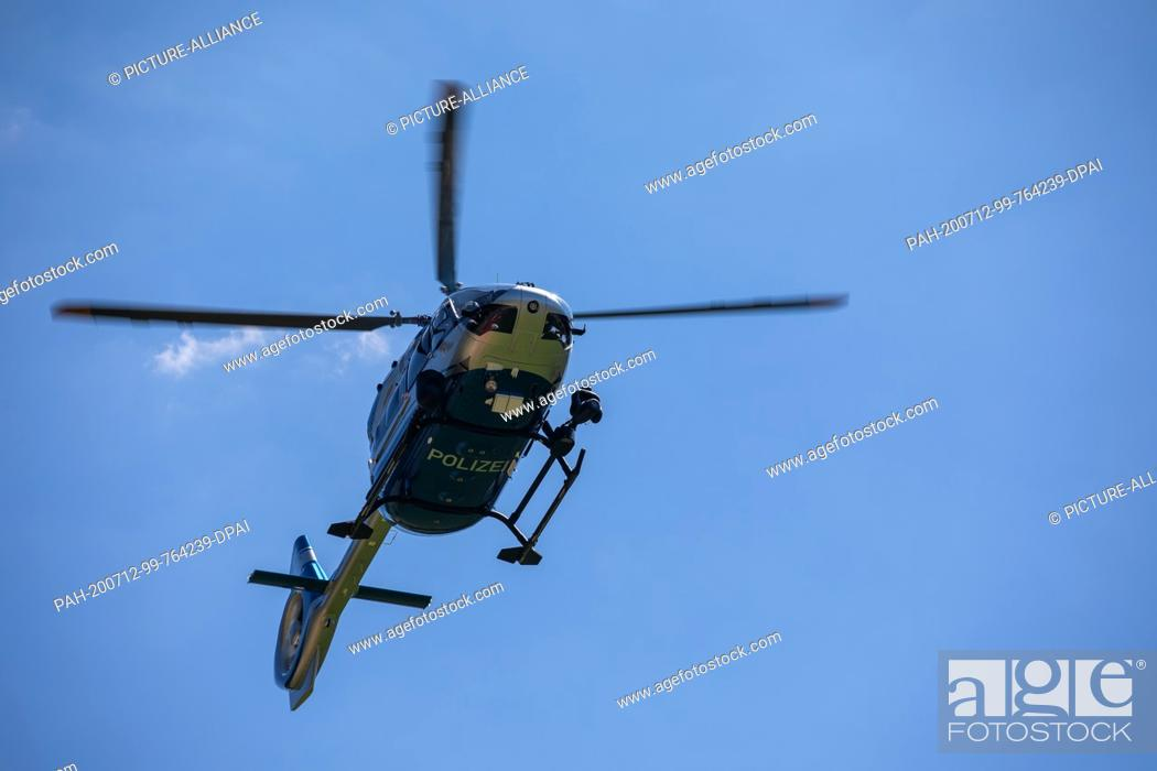 Stock Photo: 12 July 2020, Baden-Wuerttemberg, Oppenau: A police helicopter hovers in the air near the site. A man armed with bows and arrows has threatened police officers.