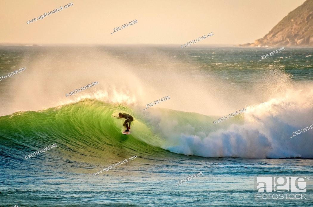 Stock Photo: Luminesent Green waves with Surfer emerging off The Cape, South Africa.