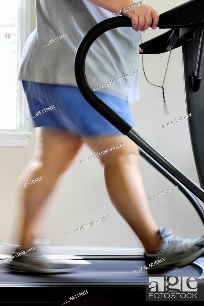 Stock Photo: Overweight woman walking on treadmill, USA.