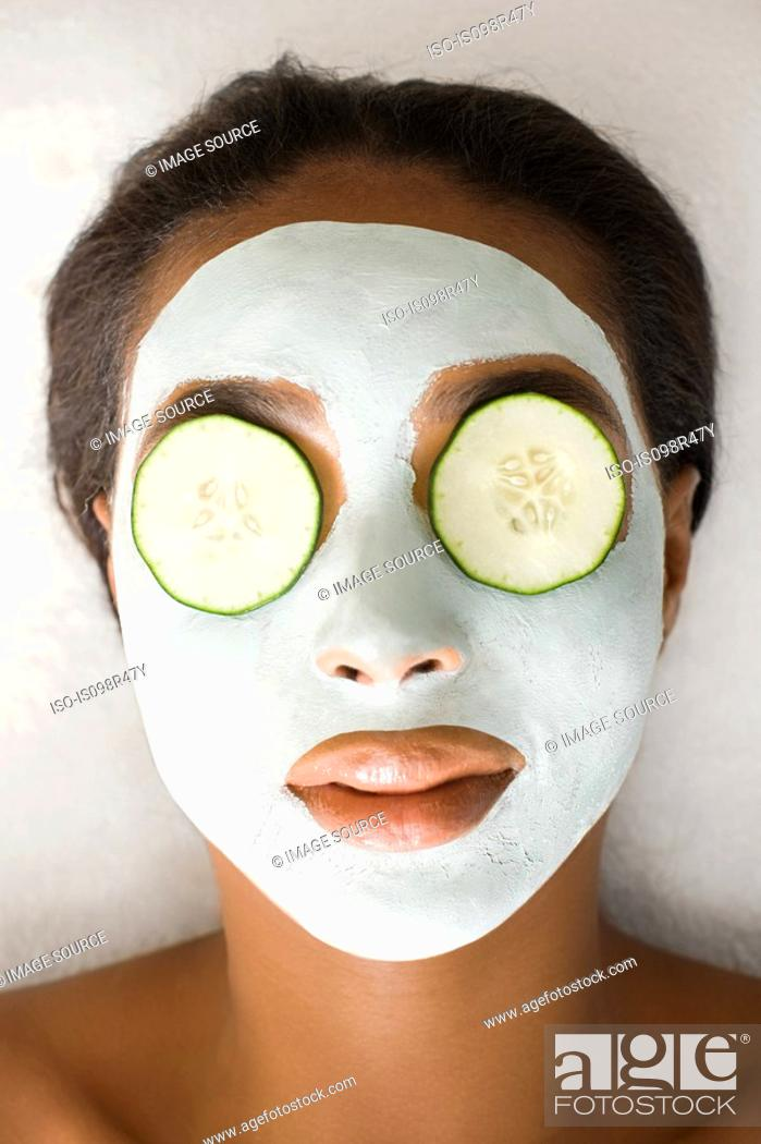 Stock Photo: Woman wearing face mask and cucumber.