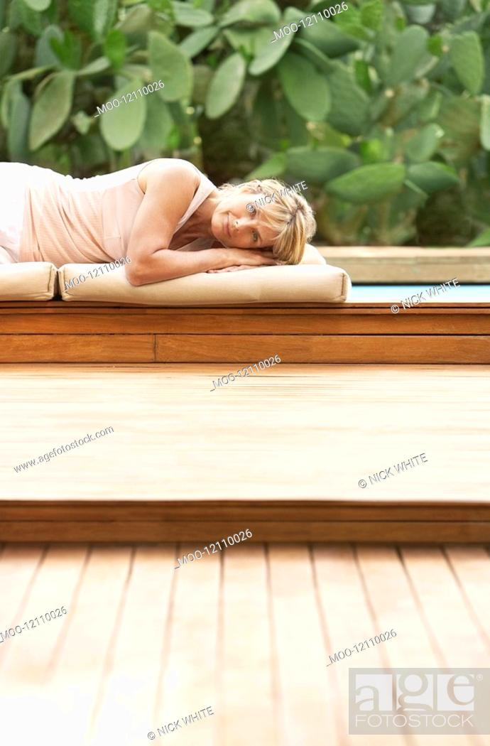Stock Photo: Middle-aged woman lying on cushions by pool portrait.