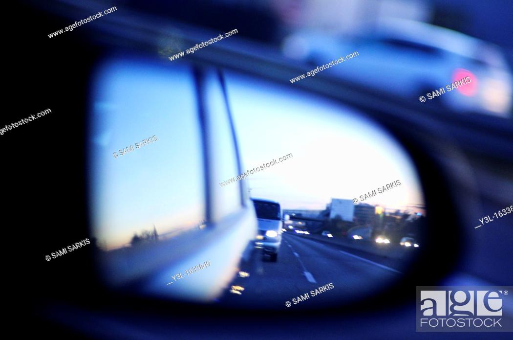 Stock Photo: Traffic on highway reflected by side-view mirror at dusk, blurred motion.
