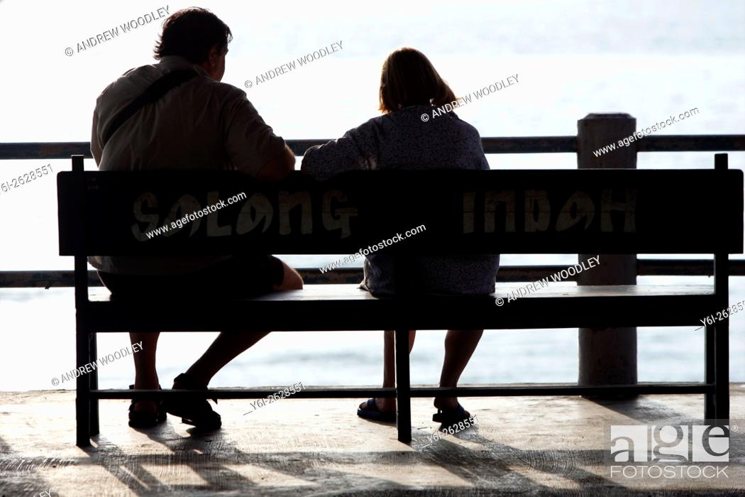 Stock Photo: Couple sit at end of pier Salang Beach Tioman Island Malaysia.
