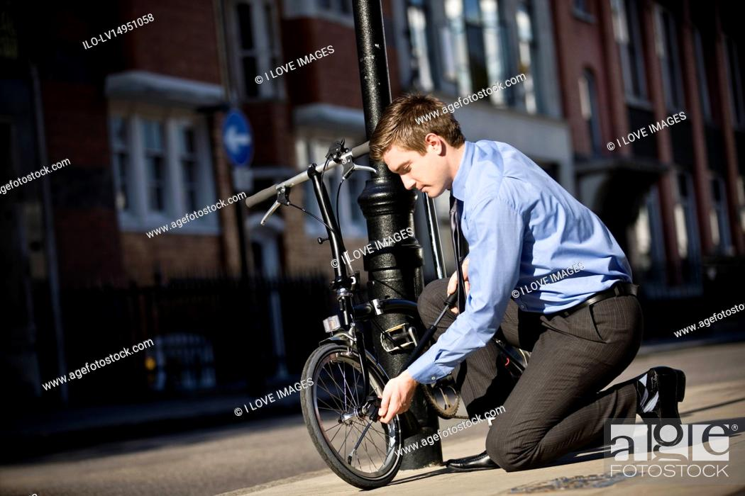 Stock Photo: A businessman pumping up the tires on his bicycle.