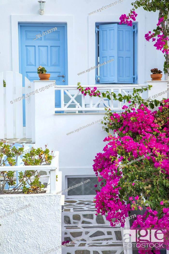 Stock Photo: Traditional Greek home with pink bougainvillea flowers and blue windows in Oia, Santorini Greece.