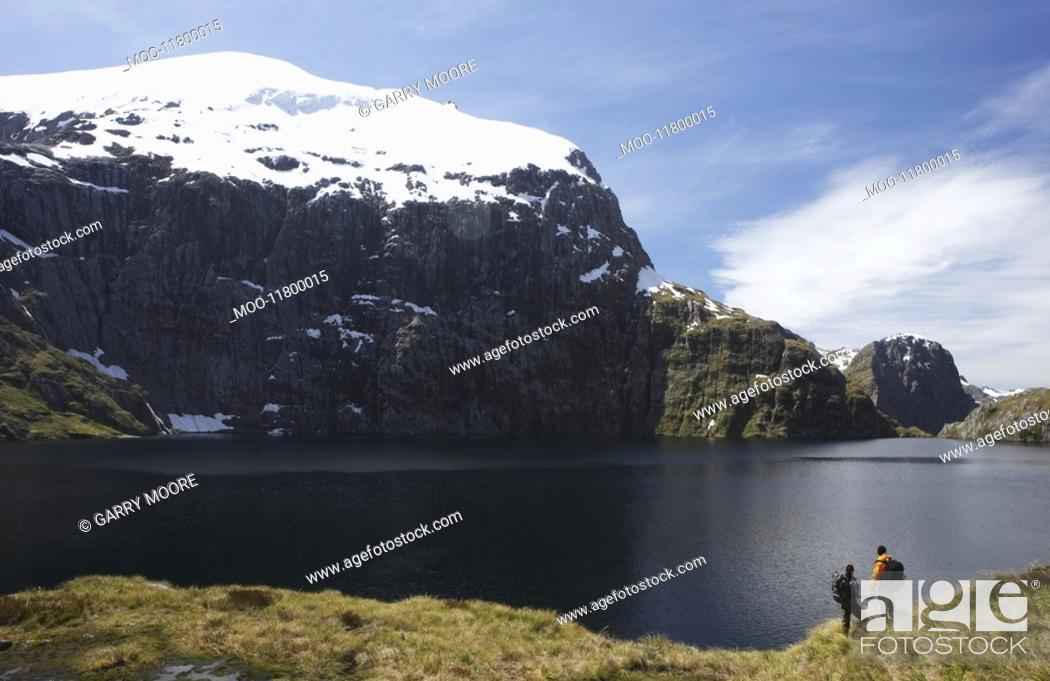 Stock Photo: Two hikers looking at mountain lake.