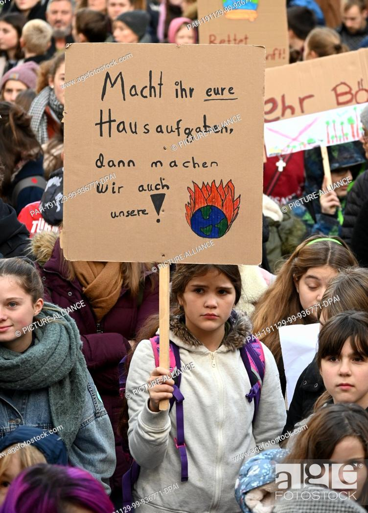 """Stock Photo: 29 November 2019, North Rhine-Westphalia, Cologne: Students hold a demonstration for climate protection with protest signs saying """"""""Do your homework."""