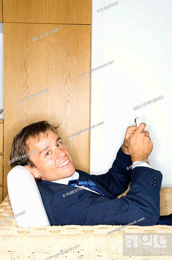 Stock Photo: Portrait of a businessman sitting in an armchair and holding a mobile phone.